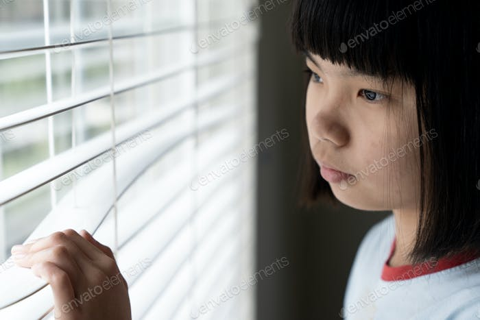Sad little girl standing near the window