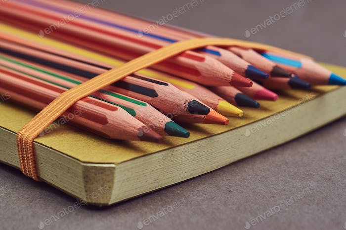Multicolored pencils lying on a yellow notepad.
