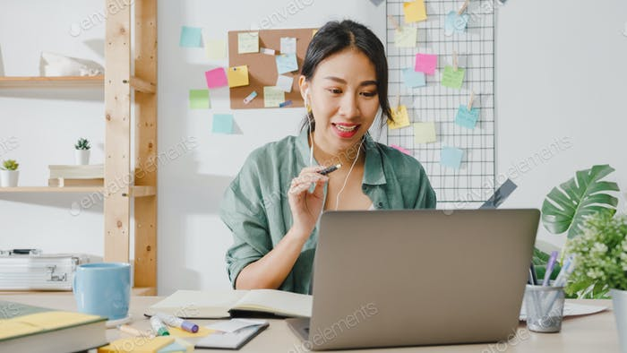 Asian business woman using laptop talk to colleagues in video call while smart working from home.