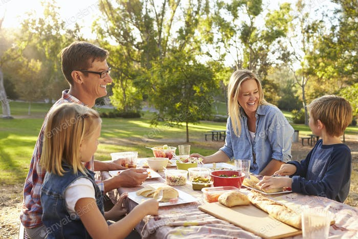 Young white family enjoying a picnic at a table in a park