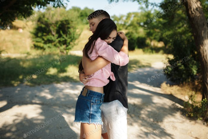 Couple standing and embracing each other while thoughtfully closing their eyes in park