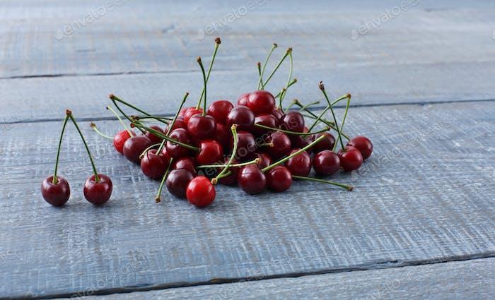 Sweet fresh cherries on blue rustic wood