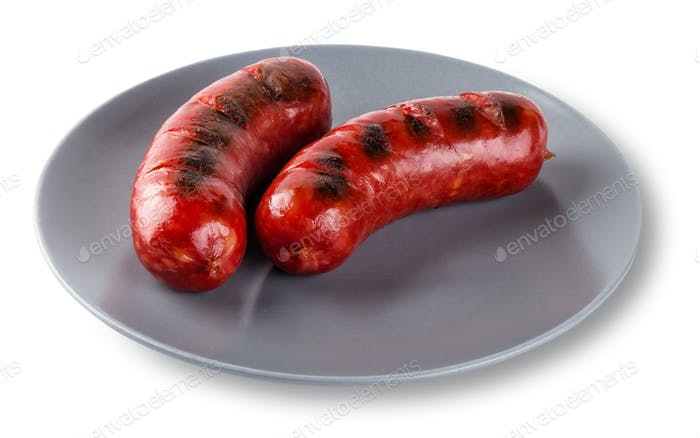 Two fried sausages on gray plate isolated on white background