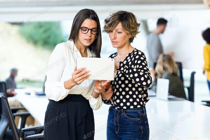 Zwei kluge junge Geschäftsfrauen sprechen über die Arbeit mit digitalen ta