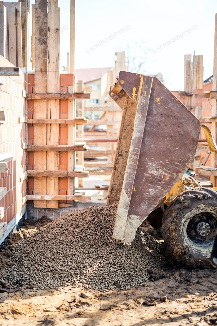 Kipper Entladen Bau Kies, Granit und Schotter bei Baufundament