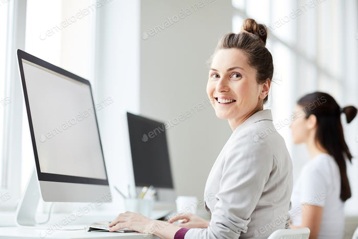 Smiling Woman Using Computer in Office