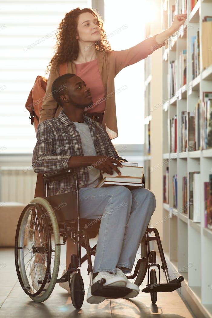 Mädchen hilft Student mit Behinderung