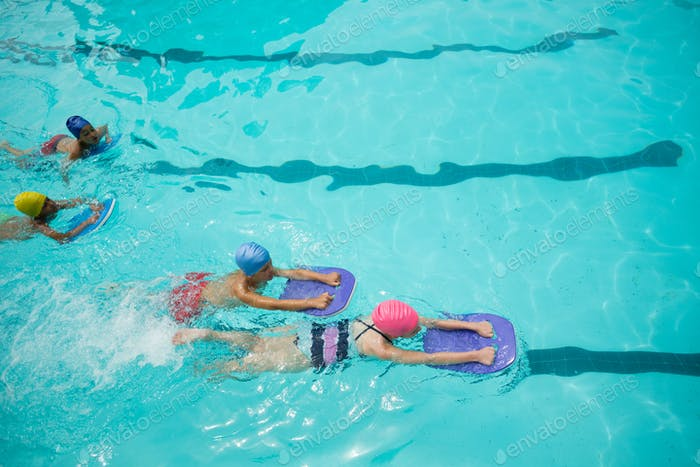 Girls and boys using kickboard while swimming in pool