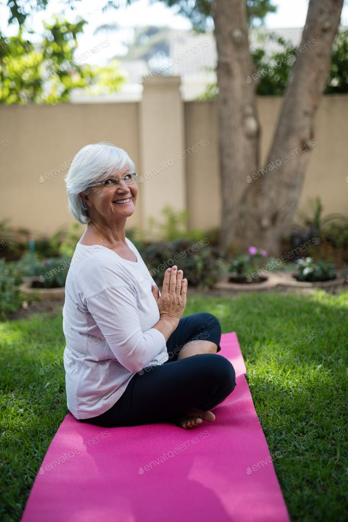 Side view of smiling senior woman meditating in prayer position