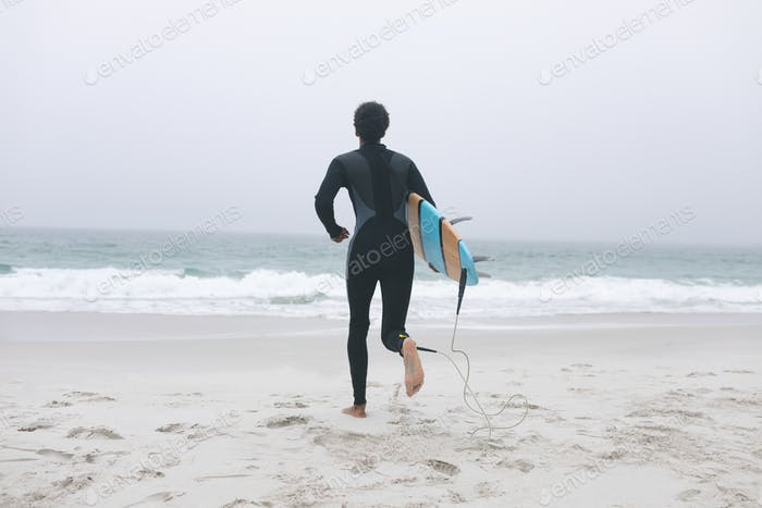 Rear view of young mixed-race male surfer running on the beach with his surfboard