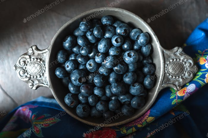 Tin bowl with blueberries, colored napkin on slate