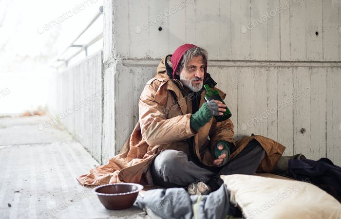 A front view of homeless beggar man sitting outdoors, holding bottle of alcohol. Copy space.
