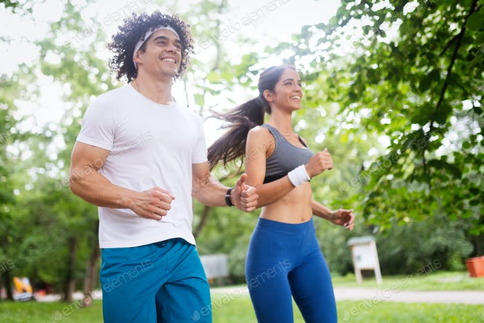 Happy young woman doing excercise outdoor in a park, jogging