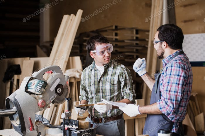Inspektor und Zimmermann diskutieren den Prozess der Herstellung von Holzprodukten für Möbel