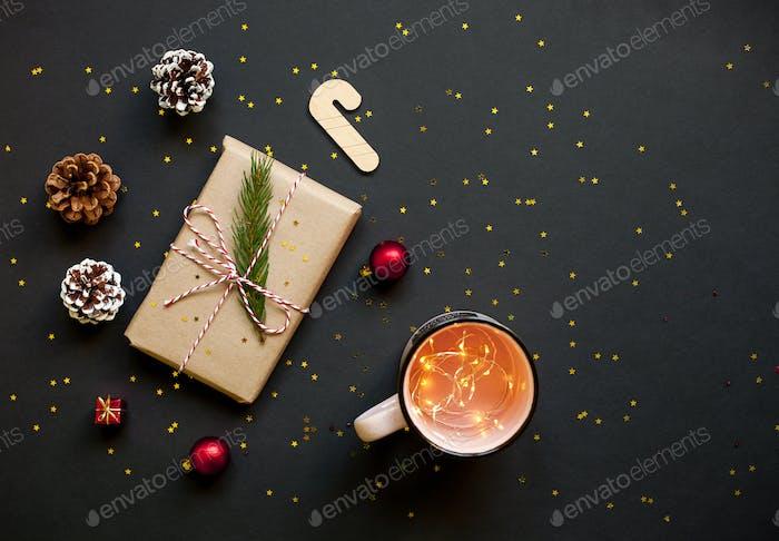 Weihnachtskarte. Geschenkbox, Tannenzweige und Dekor auf schwarzem Hintergrund.