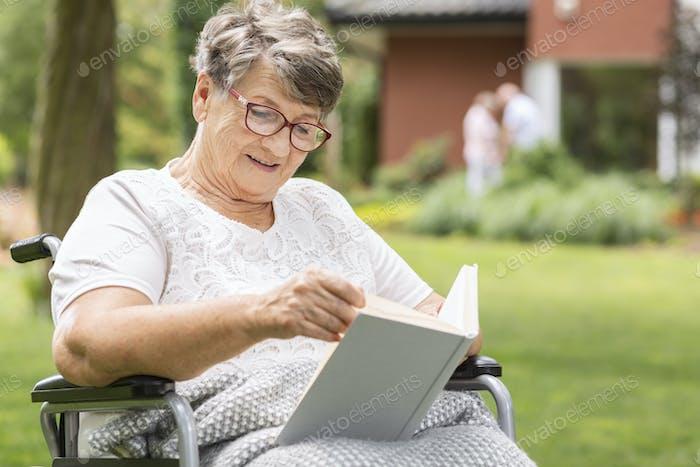 Eine ältere Frau im Rollstuhl liest ein Buch während des Sommers da