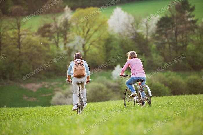 Beautiful senior couple with bicycles cycling outside in spring nature.
