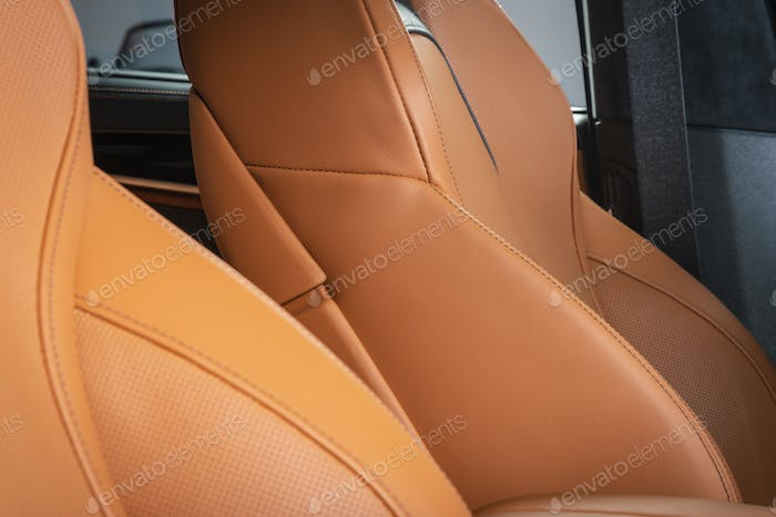 Part of red leather car seat with the car interior on the background