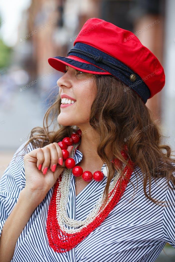 Stilvolle brünette Mädchen in einer gestreiften Bluse gekleidet, rote Perlen und eine rote Kappe Posen in der Stadtstraße