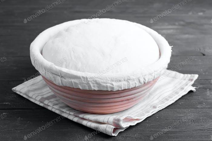 Hausgemachter frisch zubereiteter Teig für frische gesunde Backwaren und Gebäck auf einem hölzernen Küchentisch