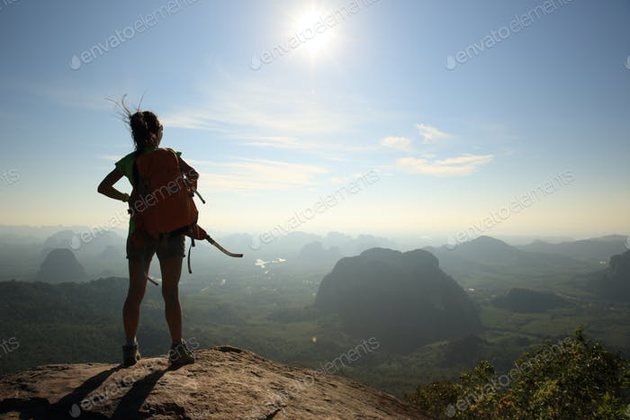 Successful hiker enjoy the beautiful sunrise view on mountain top