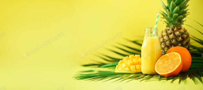 Delicious juicy smoothie with orange fruit, mango, pineapple on yellow background. Copy space. Pop
