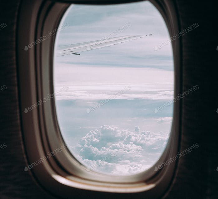 Clouds and sky through window of an aircraft.