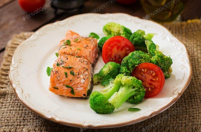 Baked fish salmon garnished with broccoli and tomato. Dietary menu. Fish menu. Seafood - salmon.