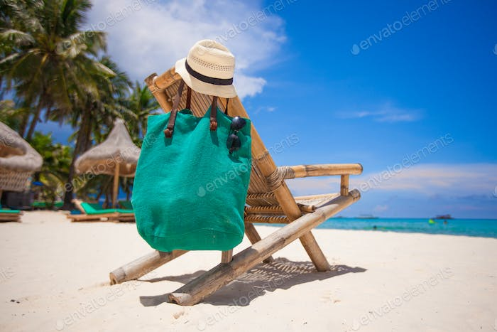 Wooden beach chair with hat and bag on white sand beach
