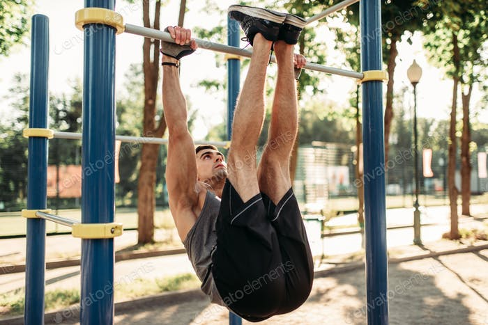 Man doing stretching exercise using horizontal bar