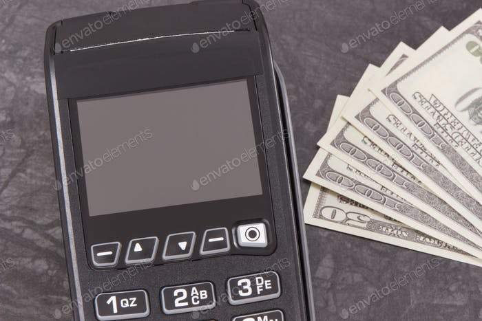 Payment terminal and curriencies dollar. Cashless or cash paying for shopping concept