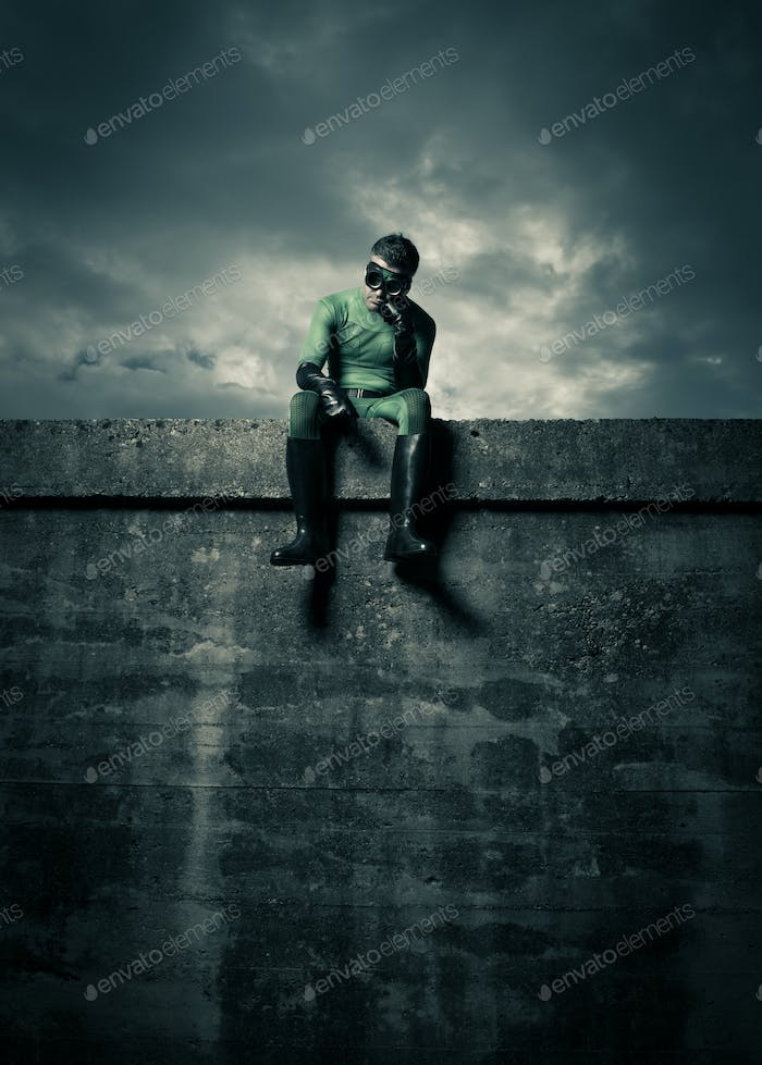Pensive superhero on concrete wall