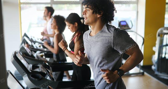 Bild von Menschen, die auf dem Laufband im Fitnessstudio laufen