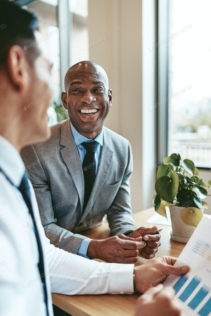 African American businessman laughing with a colleague in an office
