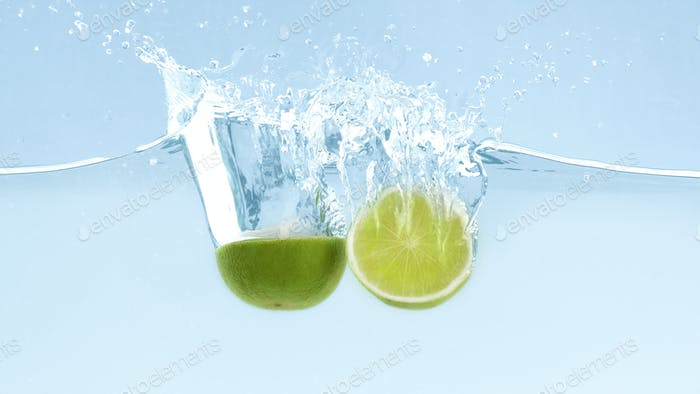Green fresh limes with clear water splash and drops