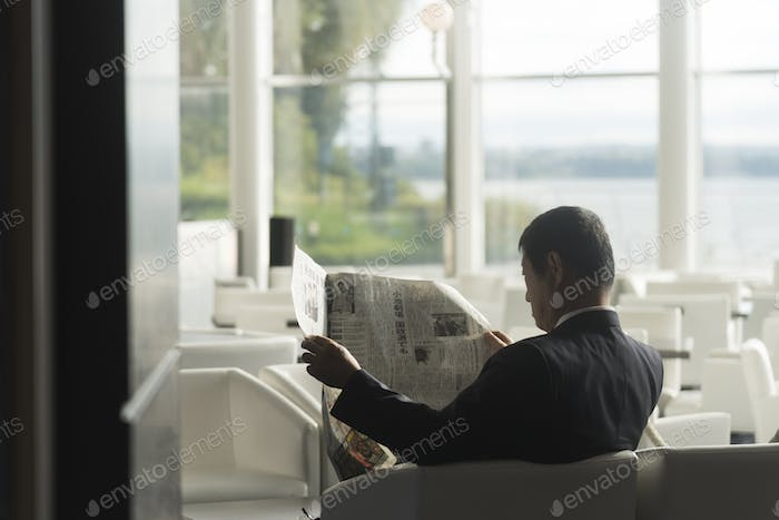 Businessmen are reading the newspaper in the morning in Fukuoka. Pic was taken in Oetober 2017.