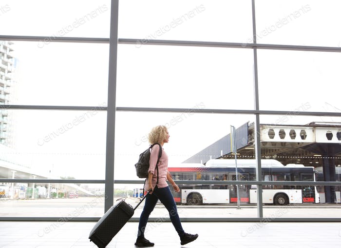 Young female traveler walking in bus station