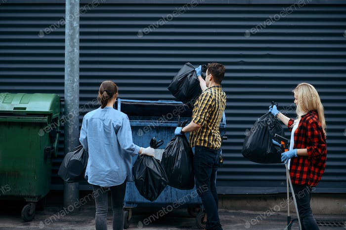 Volunteers puts plastic trash bags into the can