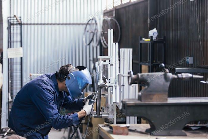 Unrecognizble man welding iron details