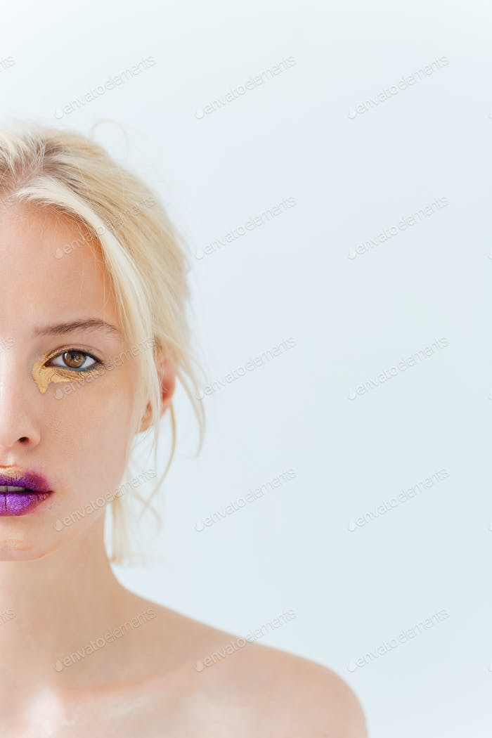 Half face of beautiful young woman with purple stylish makeup