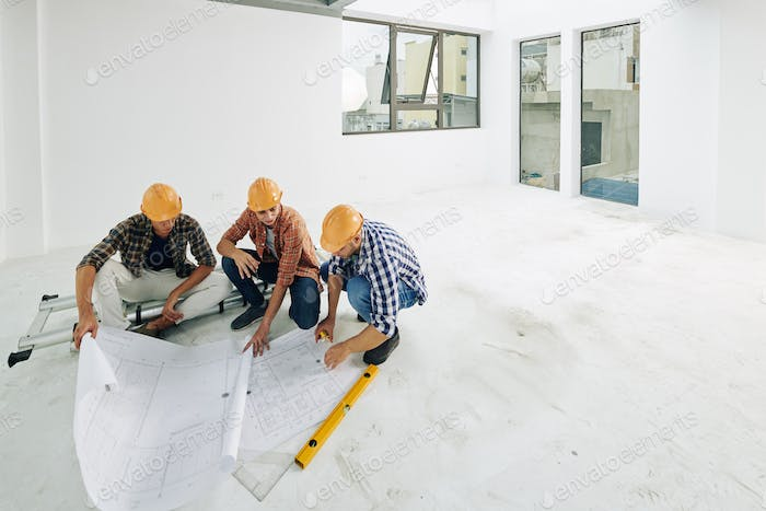 Builders checking blueprints