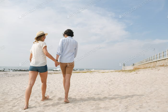 Low angle view of young Caucasian couple walking at beach on a sunny day