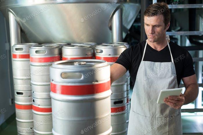 Worker examining kegs