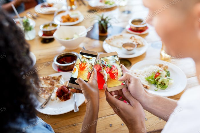 couple picturing drinks by smartphones at bar