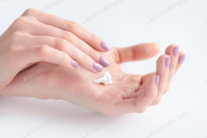 Women's hands with pink manicure applying cream. The concept of