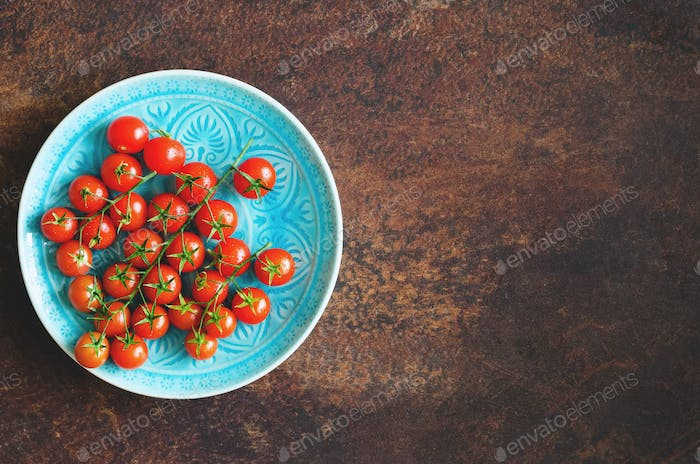 Many fresh cherry tomatoes in blue plate on brown background. Free space for your text