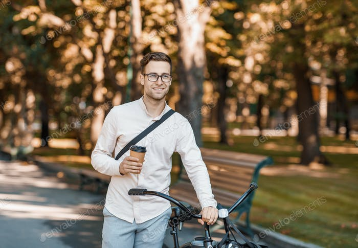 Takeaway coffee and way to work. Attractive guy with glasses and cup in hand goes with bike