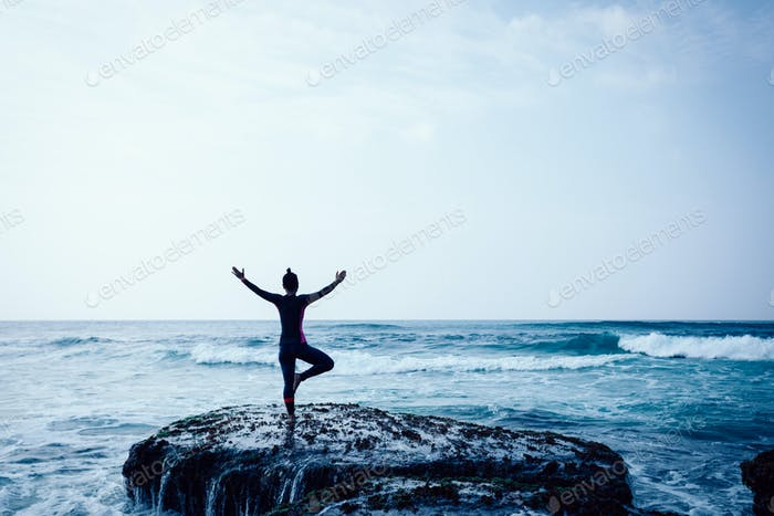 Yoga Woman outstretched arms at seaside mossy coral reef