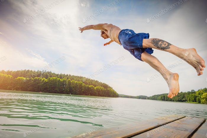 Young fit man jumping into a lake.