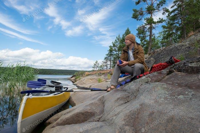 Mann sitzt am Flussufer ruht nach aktivem Paddeln
